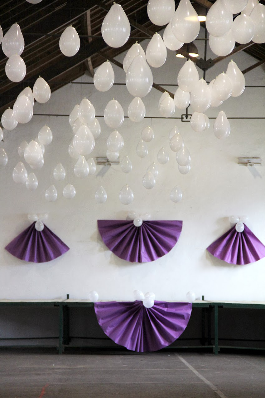 decoracion-mercado-carnaval-que-tono-de-verde-saron-cantabria-globos-blanco-morado-papel-abanicos-escenario-pared